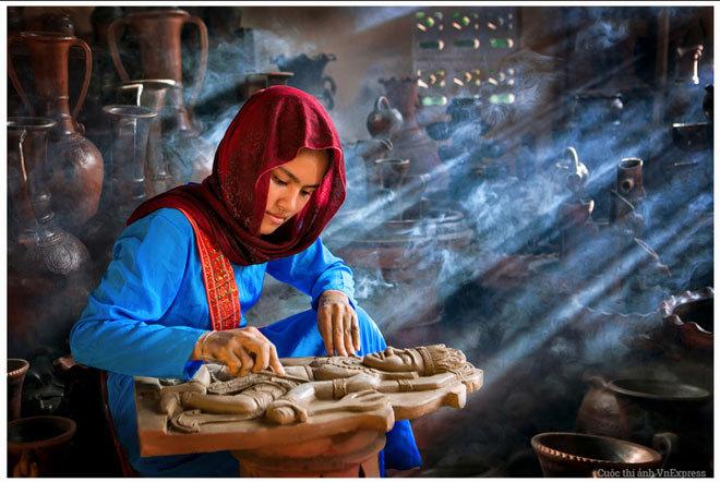 """<p> <strong>""""Thợ gốm"""" - Phạm Ngọc Thành</strong></p> <p class=""""Normal""""> Theo tác giả: """"<em>Thợ gốm</em> được sáng tác tại làng gốm Bàu Trúc, tỉnh Ninh Thuận, một làng nghề truyền thống nổi tiếng của đồng bào Chăm. Thiếu nữ trong hình, một thợ gốm lành nghề của làng, đang chăm chút từng chi tiết tác phẩm của mình trước khi đưa vào lò nung. Ánh nắng chiều xuyên qua làm toát lên vẻ đẹp huyền bí của thiếu nữ và tác phẩm"""".</p>"""