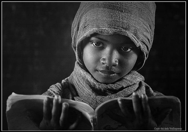 """<p> <strong>""""Đọc sách"""" - Trần Trọng Lượm</strong></p> <p class=""""Normal""""> """"Trong một ngày đi sáng tác ở một ngôi làng nhỏ, tôi tình cờ đi ngang qua một lớp học thì thấy một bé gái đang ngẫm nghĩ đọc sách với đôi mắt ngây ngô, hồn nhiên trông rất đẹp. Tôi mới chụp lại bức ảnh này"""".</p>"""