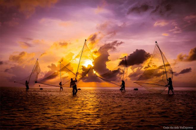 """<p> <strong>""""Điệu múa trên biển"""" - Đinh Quang Thọ</strong><br /><br /> Tác giả thực hiện bức hình trong lần về Bạc Liêu tìm hiểu nghệ thuật đánh bắt cá đặc trưng của vùng biển này, thường được gọi là """"đẩy xiệp"""". """"Buổi sáng sớm, những chàng trai lực lưỡng với vai trò là lao động chính trong gia đình tụ tập cùng nhau ra biển để đánh bắt tôm, cá, cua ghẹ ven mé nước biển. Họ mang theo những cái lưới được gắn với nhau qua hai thanh tre tạo thành công cụ giống một cái vợt lớn. Họ tụ tập thành nhóm gồm năm, bảy người cùng khai thác một điểm, sau đó lại di chuyển đến địa điểm khác khi mặt trời càng lên cao. Những tư thế họ đưa vợt xuống biển sau đó kéo lên và bỏ vào rọ đặt phía trước, cứ liên tục như một điệu múa, một vũ khúc trên biển"""", tác giả chia sẻ.</p>"""