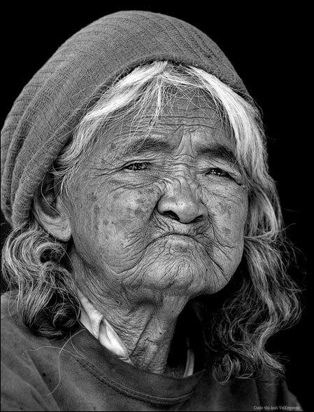 """<p> <strong>""""Chân dung Mẹ"""" - Mai Lộc</strong></p> <p class=""""Normal""""> Ảnh chụp tại một làng dân tộc Bana - làng Pleiphun, Pleiku, tỉnh Gia Lai - trong chuyến tham quan bản làng văn hóa các dân tộc Tây Nguyên. Hình ảnh người mẹ với khuôn mặt thật phúc hậu và như đang mong đợi một điều gì đó đã gây ấn tượng với tác giả. """"Vì thời gian quá vội, tôi không kịp hỏi tên mẹ. Và cũng từ dạo đó, tôi chưa có dịp trở lại thăm làng Pleiphun. Chỉ mong rằng nơi ấy mẹ vẫn sống vui khỏe cùng bản làng con cháu"""", tác giả nói.</p>"""