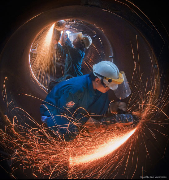 """<p> <strong>""""Đường hàn của những người thợ LILAMA"""" - Nguyễn Đăng Hồng</strong></p> <p class=""""Normal""""> """"Tôi chụp những người thợ xí nghiệp LILAMA 18-3 của Công ty CP LILAMA 18, thuộc Tổng công ty lắp máy Việt Nam tham gia chế tạo chân đế giàn khoan dầu khí, phục vụ thăm dò và khai thác dầu khí trên biển. Chân đế giàn khoan gồm những ống thép tròn, dài và dày, rất nặng. Dưới trời nắng nóng, những người thợ miệt mài hàn, mài nối những ống thép với kỹ thuật đòi hỏi rất cao dưới sự giám sát chặt chẽ. Họ phải chống chọi với cái nóng và khói hàn rất độc hại. Đó là công việc nặng nhọc nhất mà tôi từng thấy. Họ rất đáng được tôn vinh"""", tác giả nói.</p>"""