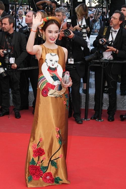 """<p> Angela Phương Trinh chiếm cảm tình của khán giả khi diện thiết kế in hình <a href=""""https://vnexpress.net/giai-tri/tin-tuc/thoi-trang/sao-dep-sao-xau/angela-phuong-trinh-dien-vay-tranh-dong-ho-den-cannes-3405132.html"""" target=""""_blank"""">tranh dân gian</a> Đông Hồ của Thủy Nguyễn đi thảm đỏ Cannes 2016. """"Bà mẹ nhí"""" phối bộ váy phom rộng cùng mấn đội đầu cách điệu và ví cầm tay hình chú chim đính đá. Sự kết hợp này giúp cô nhận được nhiều lời khen khi khéo léo giới thiệu tinh thần Việt trên thảm đỏ quốc tế.</p>"""