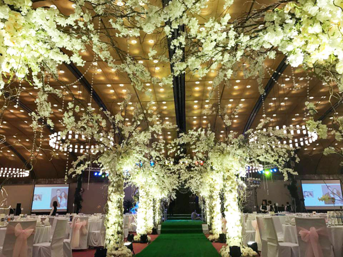 """<p class=""""Normal""""> Hoa trắng được trang trí ở trần nhà và những cổng vòm, lối đi lên sân khấu.</p>"""