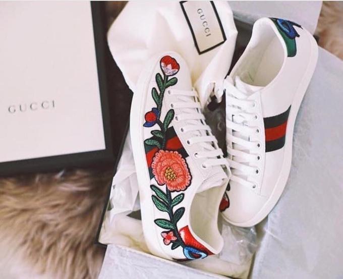 """<p class=""""Normal""""> Ra mắt năm 2015, Gucci ACE Low-top Floral là một trong những sản phẩm thành công của hãng mốt kể từ khi Alessandro Michele chèo lái. Chiếc giày màu trắng thêu hoa trên thân làm say lòng những tín đồ cuồng thời trang phi giới tính. Một đôi Gucci thêu hoa có giá 695 USD (khoảng 15,7 triệu đồng).</p>"""