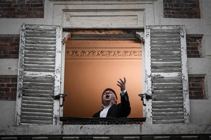 Ca sĩ opera Pháp - Stephane Senechal - trình diễn ca khúc O sole mio từ cửa sổ nhà anh ở Paris. Ảnh: AFP.