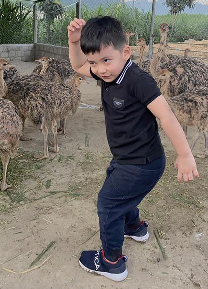 Bé Nu (ba tuổi) tạo dáng giống đà điểu.