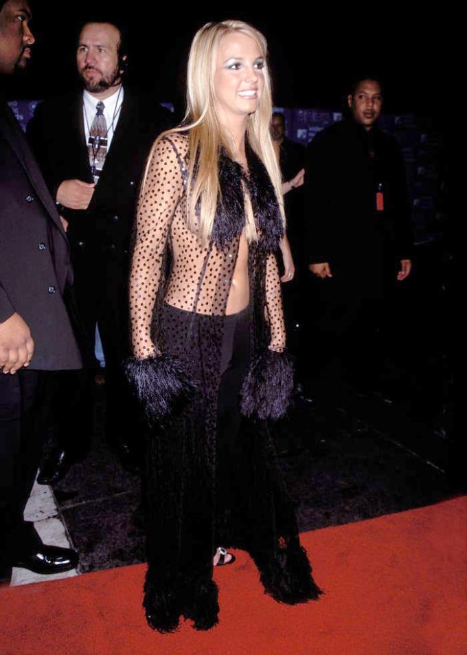 Britney để ngực trần lên thảm đỏ với áo chấm bi nhấn lông vũ ở ngực, tay, kết hợp kiểu tán phấn mắt ấn tượng của thập niên 1990 ở lễ trao giải VMAs 1999.