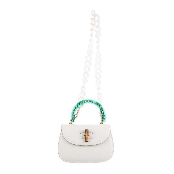Túi đeo vai của Gucci ghi điểm với phần tay cầm màu xanh, trang trí hạt màu lấp lánh, khóa bằng tre kết hợp dây đeo nhựa có thể tháo rời. Phụ kiện nằm trong BST 2018, làm từ da màu trắng ngà, bên trong lót vải satin nhiều màu. Sản phẩm sang tay với giá hơn 100 triệu đồng.