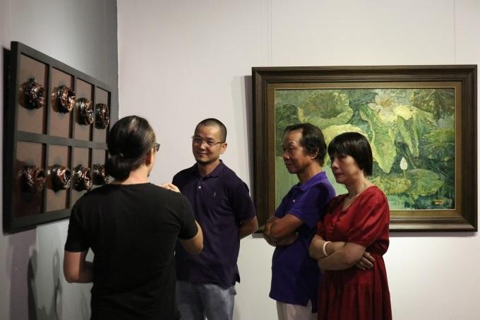Họa sĩ Phùng Huy (áo đen, bên trái) chia sẻ với người xemvề Giếng. Triển lãm lần này anh đem tới ba tác phẩm đặc tả Giếng I, Giếng II và Bóng ghế. Trong đó, anh sử dụng kỹ thuật sơn mài đắp nổi trong Giếng, tạo hiệu ứng 3D. Ảnh: Bảo Thư.