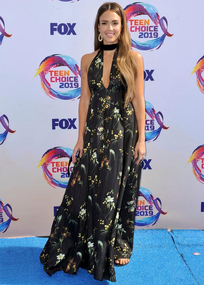 Jessica Alba được fan khen lộng lẫy với váy Oscar de la Rentatạisự kiện Teen Choice ở Los Angeles. Maxi tạo điểm nhấn với họa tiết hoa vàng - trắng, kết hợp cổ xẻ sâu tôn vòng một. Cô phối kèmdải lụa buộc quanh cổ và khuyên tai bản to của hãng Jennifer Meyer Large.