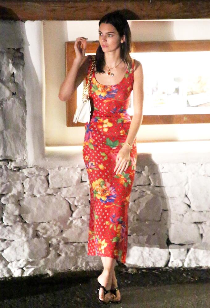 Tháng 7/2019, trong chuyến du lịch biển, siêu mẫu Kendall Jenner khoe hình thể bằng váy maxi hoa nền đỏ nổi bật. Cô mix cùng túi đeo vai màu trắng Prada và dép xỏ ngón Simon Miller.