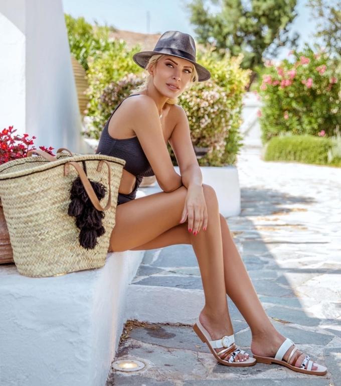 Cô được khen cá tính khi phối mũ cao bồi, túi cói bản to với áo tắm một mảnh khoét eo, bất đối xứng vai.