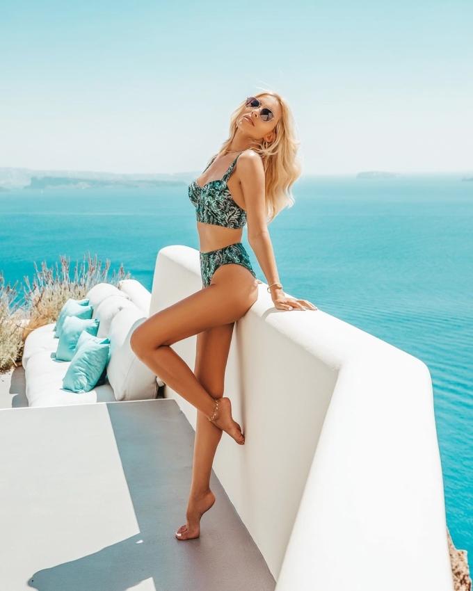 Katerina Kainourgiou khuyên phái nữ nên tạo dáng với bikini họa tiết, phối màu xanh ngọc và đen khi chụp ảnh tại đảo thiên đường Santorini - nơi có những ngôi nhà trắng muốt, mái vòm xanh xếp chồng lên nhau men theo vách núi ven biển.