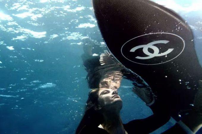 Năm 2014, trong chiến dịch Chanel No.5 do Baz Luhrmann làm đạo diễn, Gisele Bünchden lặn dưới nước. Bên cạnh cô là chiếc ván lướt sóng của làm từ gỗ sơn mài với tinh thần tối giản màu đen trắng, logo hai chữ C lồng vào nhau kinh điển. Ảnh: Chanel.