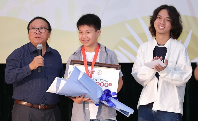 Nhà thơ Trần Đăng Khoa (trái) trao giải cho bé Cao Khải An (12 tuổi, giữa). Ảnh: Hòa Nguyễn.