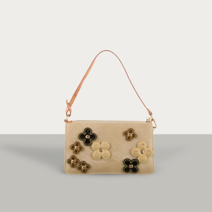 Mẫu túi xách của thương hiệu Louis Vuitton được chế tác từ chất liệu da vernis cùng họa tiết monogram đặc trưng. Nhà sản xuất tạo điểm nhấn với 8 bông hoa trang trí ở mặt trước túi, cùng chi tiết kim loại bằng đồng với tông vàng sang trọng. Túi có thiết kế ngăn chứa đồ lớn với khóa zip kéo bên ngoài. Sản phẩm hết hàng ngay khi mở bán với giá 15,42 triệu đồng. https://joolux.com/i/tui-xach-louis-vuitton-vernis-fleurs-lexington/17191