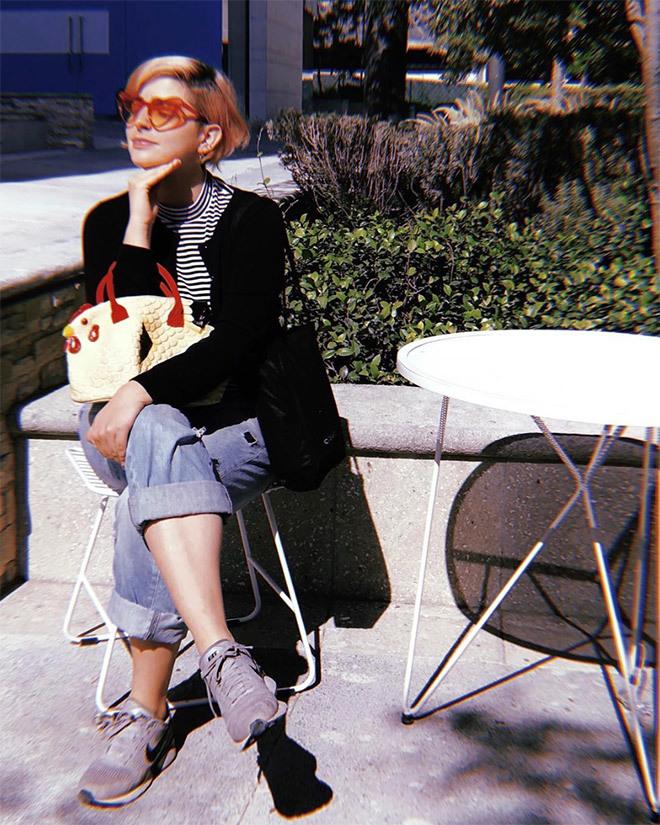 Một tín đồ thời trang phối áo khoác nhung, áo thun kẻ ngang và quần jeans theo phong cách cổ điển, kết nhấn bằng phụ kiện gồm túi gà và kính trái tim.
