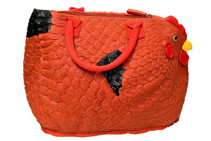 Mẫu túi ban đầu chỉ có màu vàng sản xuất từ năm 2013, sau đó có thêm phiên bản màu đỏ. Ngoài túi xách tay cỡ trung bình, hãng còn làm ví đựng tiền hình con gà. Ảnh: Amazon.