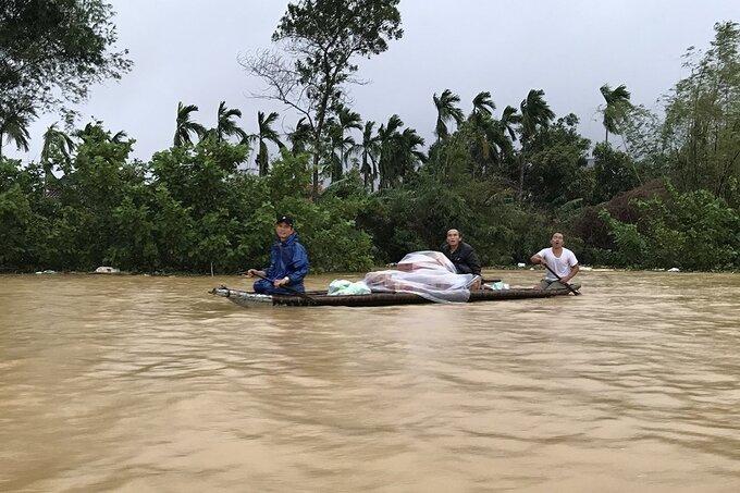 Người dân xã Hương Toàn (thị xã Hương Trà) chèo thuyền giữa nước lũ nhận mì tôm, nhu yếu phẩm cứu trợ. Ảnh: Hoàng Táo.
