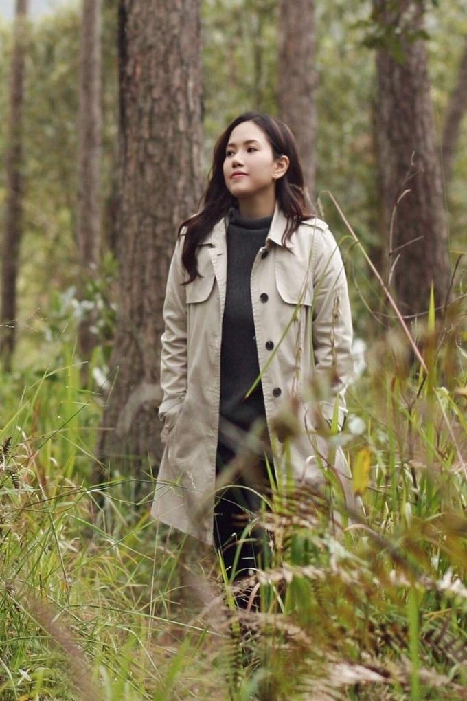 Thùy Chi phối áo khoác dáng dài với trang phục tông đen bên trong khi đi dạo trong mùa đông.
