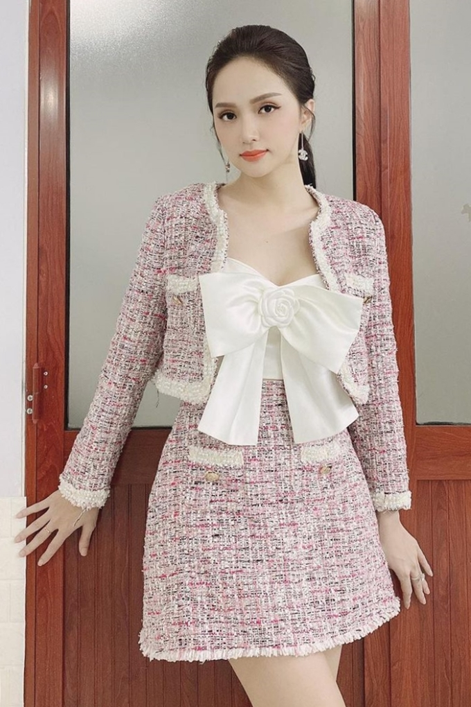 Hương Giang tạo điểm nhấn cho bộ váy suit với crop-top đính nơ bản to. Tweed được dệt đan xen bởi các sợi len có màu sắc và kích thước lớn nhỏ khác nhau, là chất liệu đặc trưng của Chanel từ những ngày mới ra mắt. Với các đặc tính giữ ấm, chống nước và không nhăn, tweed trở thành loại vải không thể thiếu mỗi mùa thu đông.