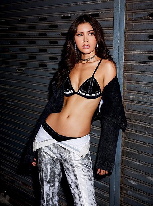 Minh Tú chọn phong cách mạnh mẽ với bikini đen và áo khoác, quần denim màu bạc.