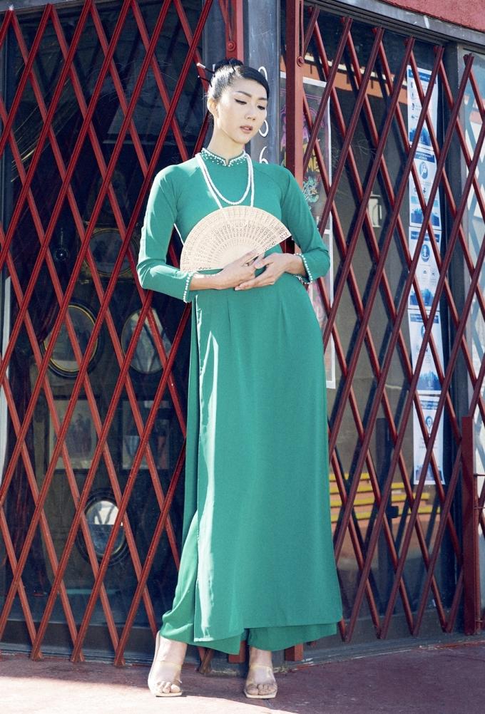 Người đẹp mặc áo dài màu xanh với phần cổ, tay áo đính ngọc trai trong bộ sưu tập Nét Á do chính cô thiết kế. Cô nói: Dù ở Mỹ, tôi vẫn thường diện trang phục truyền thống trong những dịp lễ, Tết. Tôi tin rằng những người con xa xứ đều có chung cảm giác muốn hướng về nguồn cội.