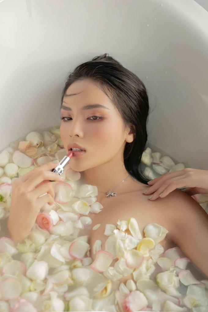 Hoa hậu trang điểm phong cách trong suốt, tạo dáng trong bồn tắm chứa đầy cánh hoa hồng.