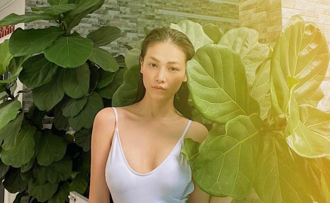 Người đẹp tạo dáng trong bộ swimwear và mốt tóc ướt trong một góc vườn.