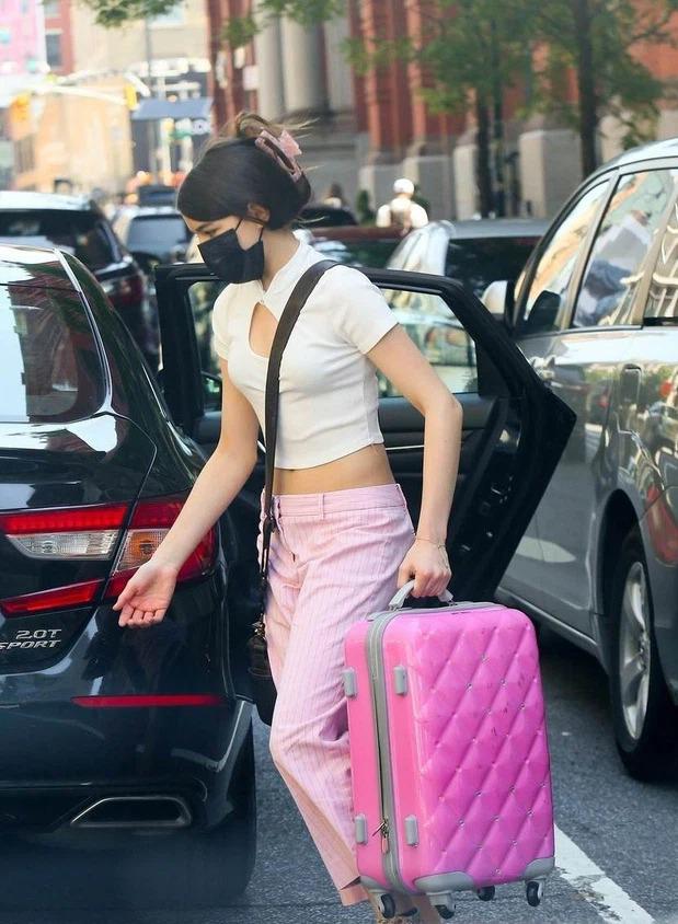 Hồi tháng 6, Suri xách vali rời nhà một mình trong chiếc áo khoét ngực và quần kẻ hồng phấn. Giống hồi bé, cô vẫn yêu thích quần áo, phụ kiện màu hồng. Ảnh: Splash News.