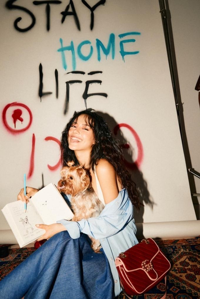 Khánh Linh là một trong những fashionista đầu tư phông nền nhiều nhất cho những bộ ảnh tại nhà. Cô lắp đặt máy chiếu, bày bàn tiệc, cắm hoa và vẽ chữ Stay home để khuyến khích khán giả ăn mặc đẹp, tìm những niềm vui riêng trong thời dịch.
