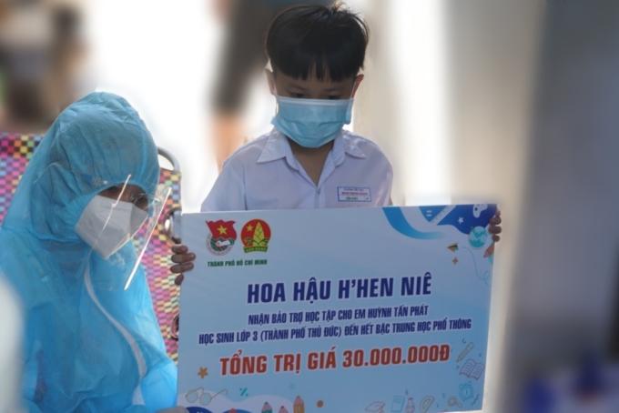 HHen Niê trao 30 triệu đồng tiền hỗ trợ học phí đến hết bậc THPT cho em Huỳnh Tấn Phát. Sau đó, cô tiếp tục đi trao quà cho những người dân ở khu phong tỏa cùng đội tình nguyện viên nghệ sĩ. Ảnh: nhân vât cung cấp.