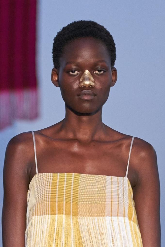 Trong buổi trình diễn của thương hiệu Kenneth Ize, chuyên gia trang điểm Fara Homidi đã mang đến nét đột phá với những mảng nhũ vàng gold trên toàn bộ sống mũi hoặc bầu mắt của người mẫu. Ảnh: Gorunway